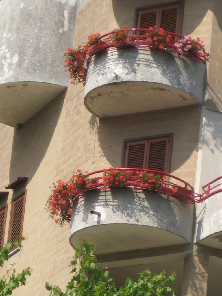 I terrazzini di Aurelio Rizzo adornati con gerani rossi